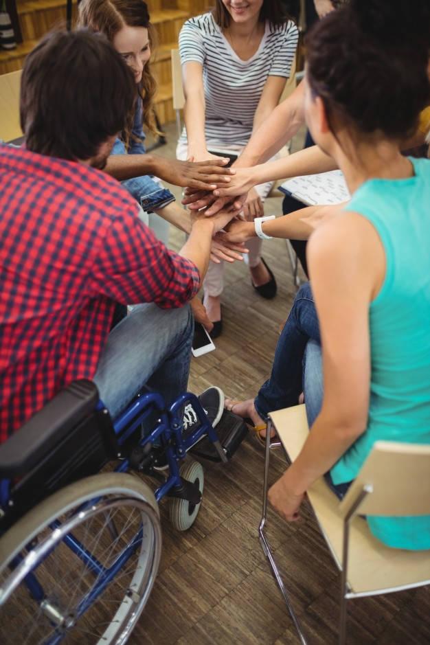 mozgássérült csapattag kezek egymáson