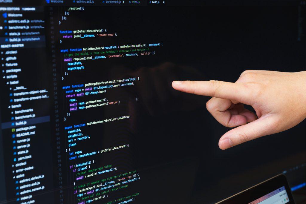 Hogyan tanuljunk programozni? Monitoron mutatja egy kéz.