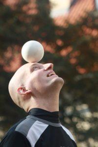 labdát fején egyensúlyozó férfi zsonglőr
